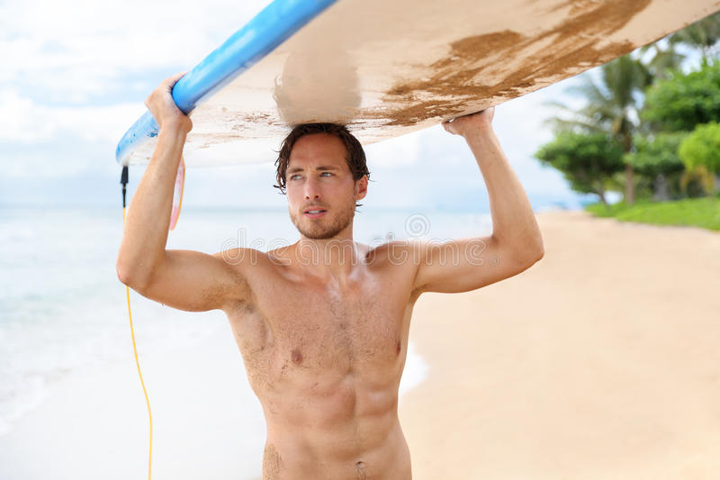 Homme sexy de surfer tenant le panneau de ressac après avoir surfé photos stock