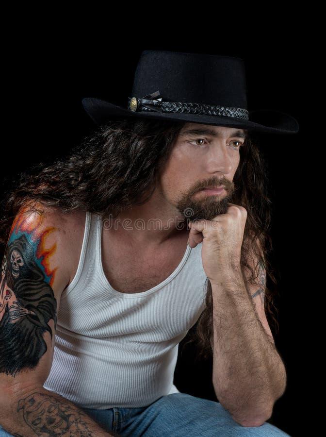 Homme sexy dur avec de longs cheveux et un chapeau de cowboy images libres de droits