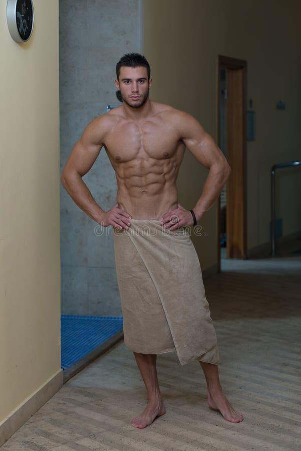 Homme sexy musculaire humide enveloppé en serviette image stock