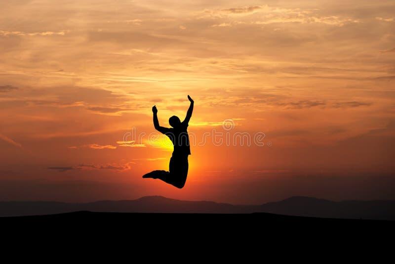 Homme silhouetté sautant dans le coucher du soleil images libres de droits