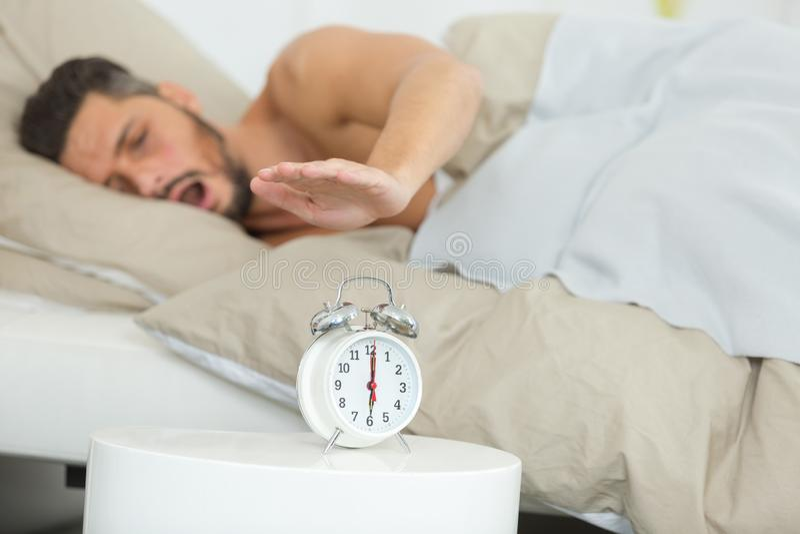Homme somnolent atteignant l'alram de sonnerie pour l'arrêter photo stock