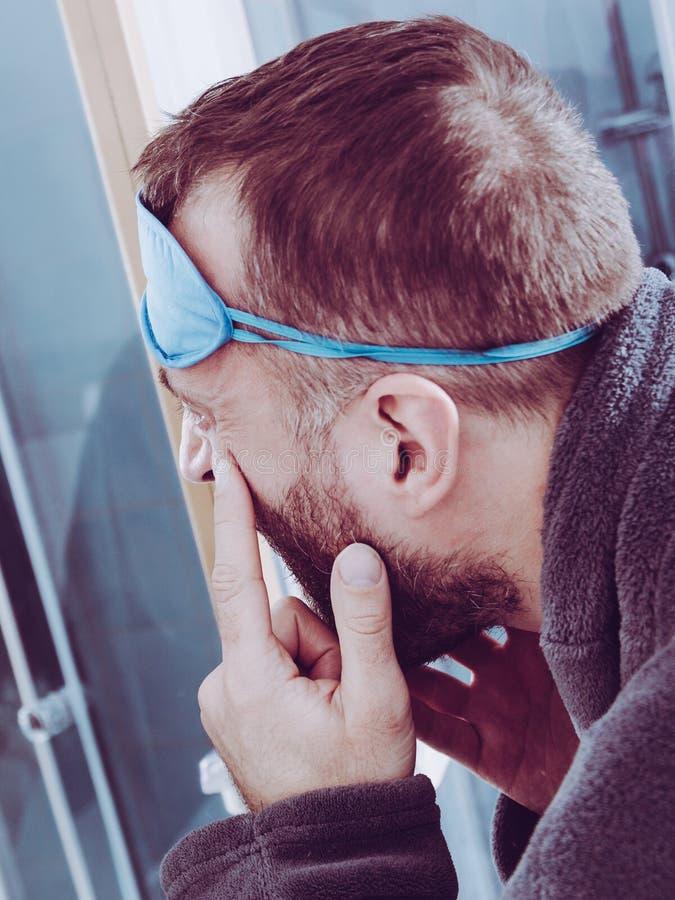 Homme somnolent regardant le miroir photo stock