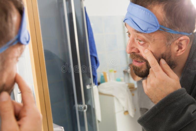 Homme somnolent regardant le miroir photographie stock