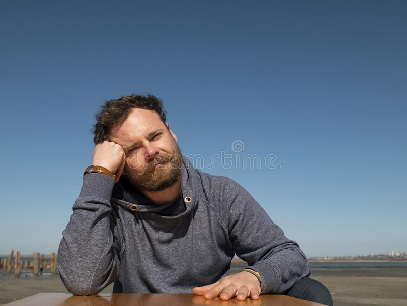 Homme songeur avec une barbe et une moustache se reposant à une table basse contre un ciel bleu photos libres de droits