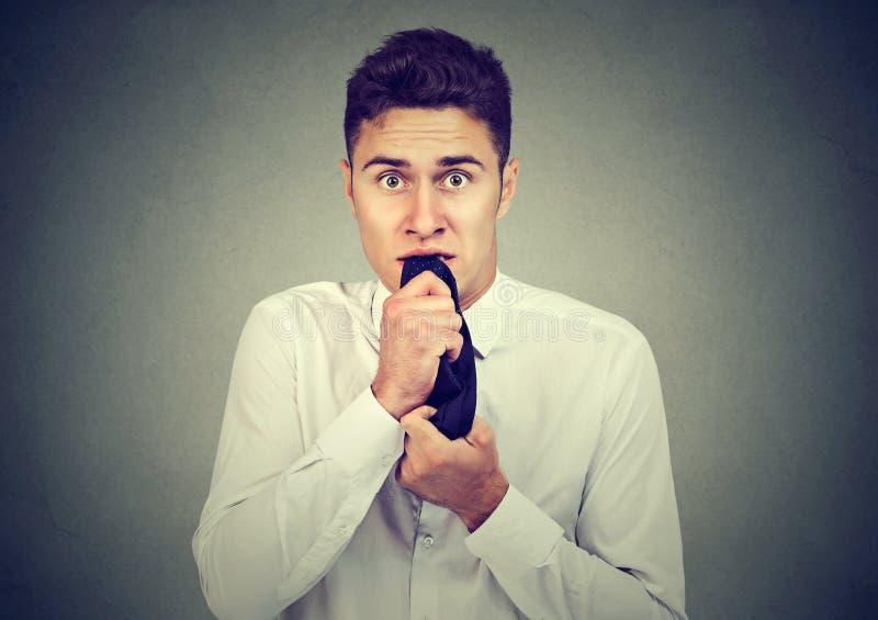 Homme soucieux d'affaires mâchant nerveusement le sien lien regardant l'appareil-photo image stock