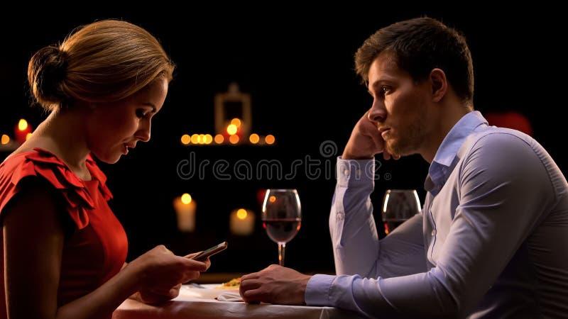 Homme soucieux regardant le smartphone faisant défiler femelle la date, remplaçant la réalité image stock