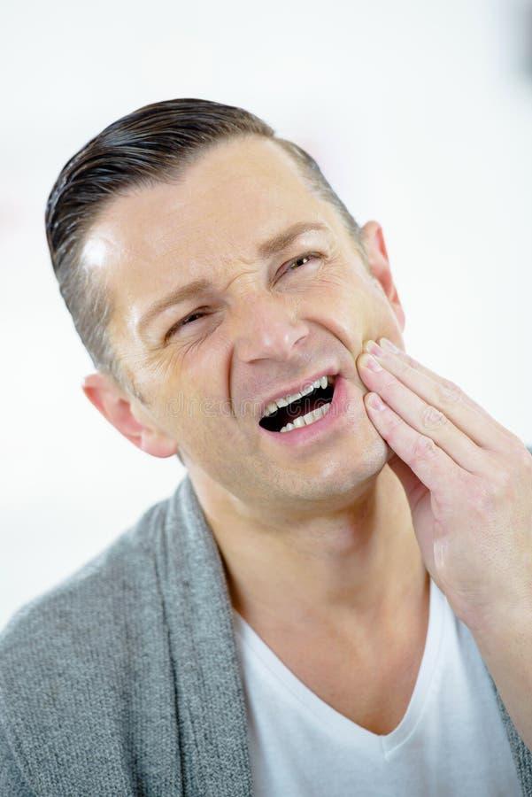 Homme souffrant du mal de dents photos stock