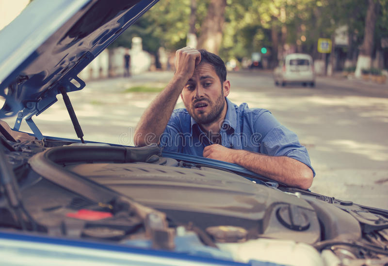 Homme soumis à une contrainte ayant des ennuis avec la voiture cassée regardant dans la frustration le moteur défaillant photographie stock libre de droits