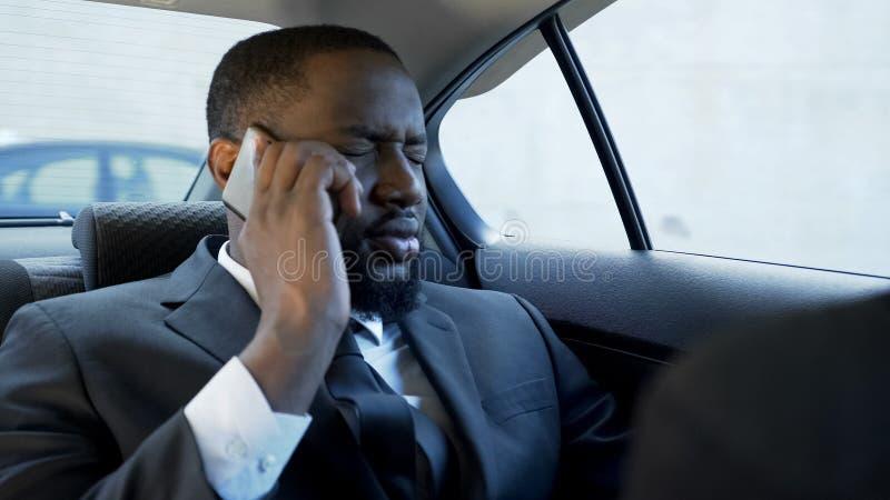 Homme soumis à une contrainte ayant la conversation téléphonique désagréable, problèmes de mariage, faillites photos stock