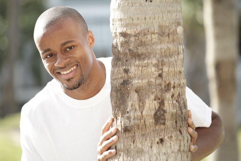 Homme souriant par derrière un arbre images libres de droits
