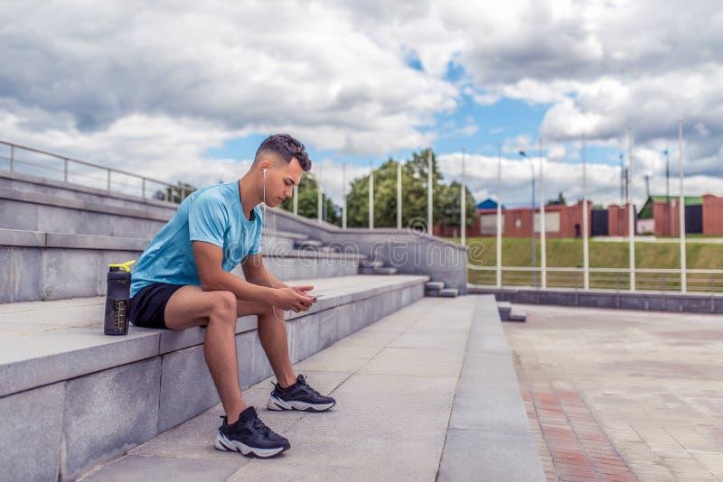 Homme sportif, étapes se reposantes, dans le téléphone de mains, réseaux sociaux de formation en ligne, musique de écoute dans le image stock