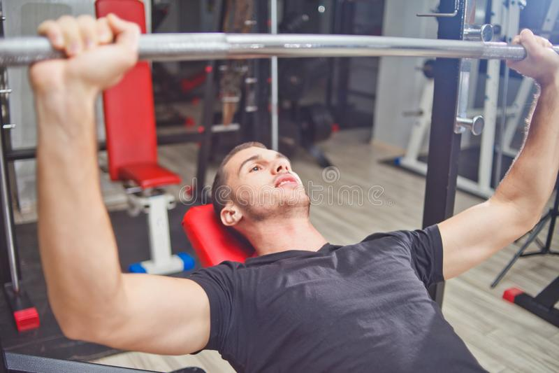Homme sportif au banc à presse soulevant un barbell photos libres de droits