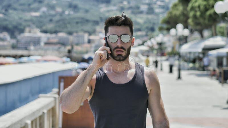 Homme sportif au bord de la mer invitant le téléphone portable image libre de droits