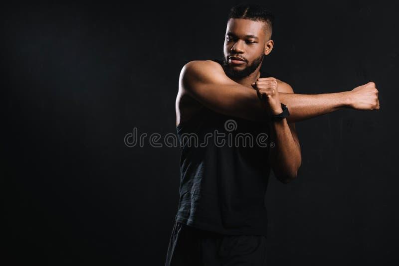 homme sportif bel d'afro-américain étirant des mains images stock