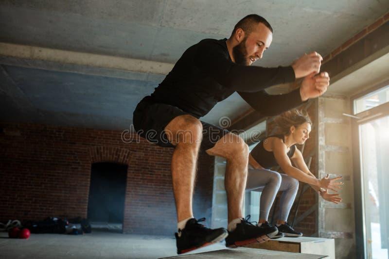 Homme sportif caucasien exécutant l'exercice de saut de boîte de plyo pendant la séance d'entraînement de crossfit photographie stock