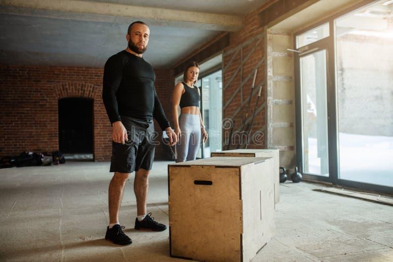 Homme sportif caucasien exécutant l'exercice de saut de boîte de plyo pendant la séance d'entraînement de crossfit photos stock