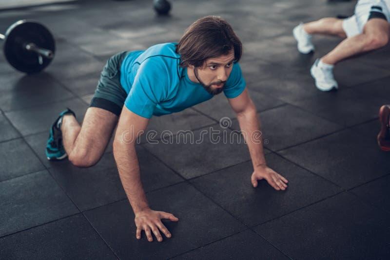 Homme sportif dans des rampements bleus de T-shirt sur le plancher de gymnase images stock