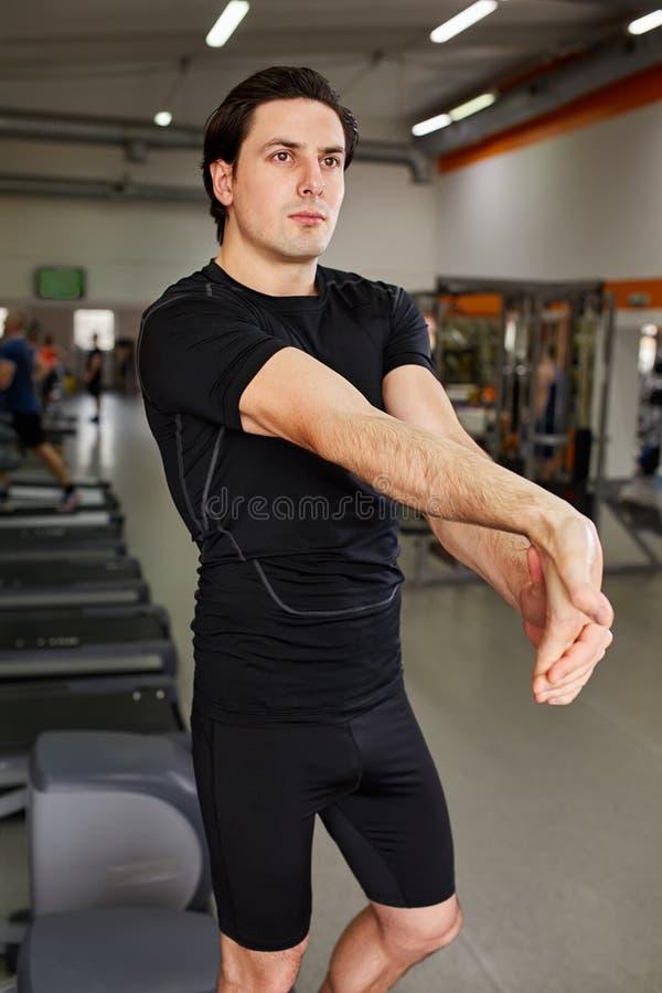 Homme sportif dans le sportwear noir étirant des bras avant séance d'entraînement de gymnase photos stock