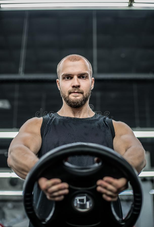 Homme sportif de bodybuilder fort brutal pompant le fond de concept de bodybuilding de séance d'entraînement de muscles - bodybui photos stock