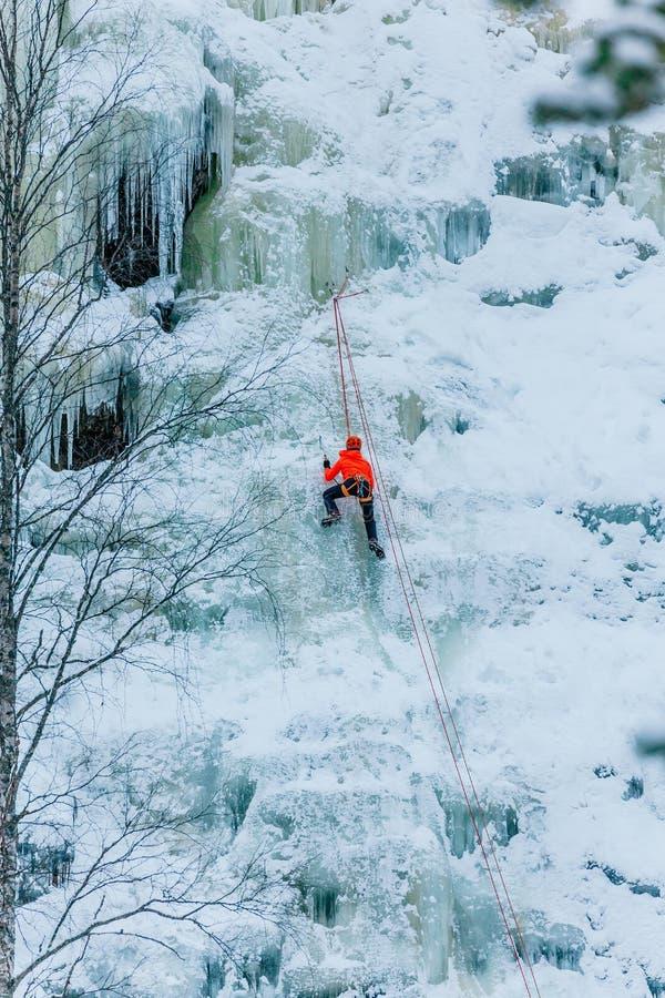 Homme sportif en escaladant un grand mur bleu de glace en Finlande photo libre de droits
