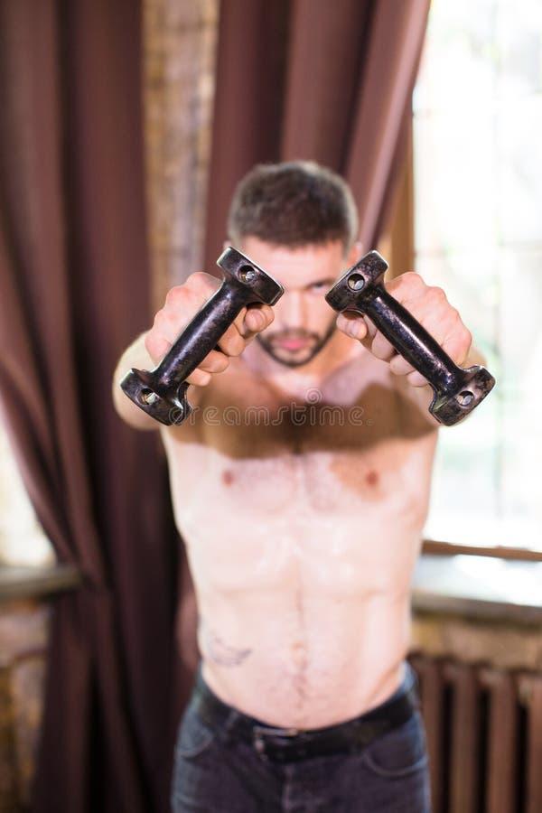 Homme sportif en sueur travaillant avec des dumbbels dans l'intérieur à la maison image stock