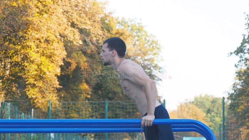 Homme sportif faisant des pousées sur des barres parallèles à l'au sol de sports en parc de ville Jeune formation musculaire fort image stock