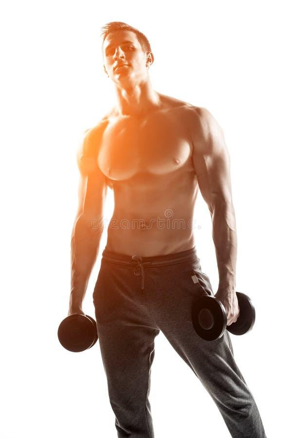 Homme sportif fort montrant le corps musculaire avec des haltères photo stock