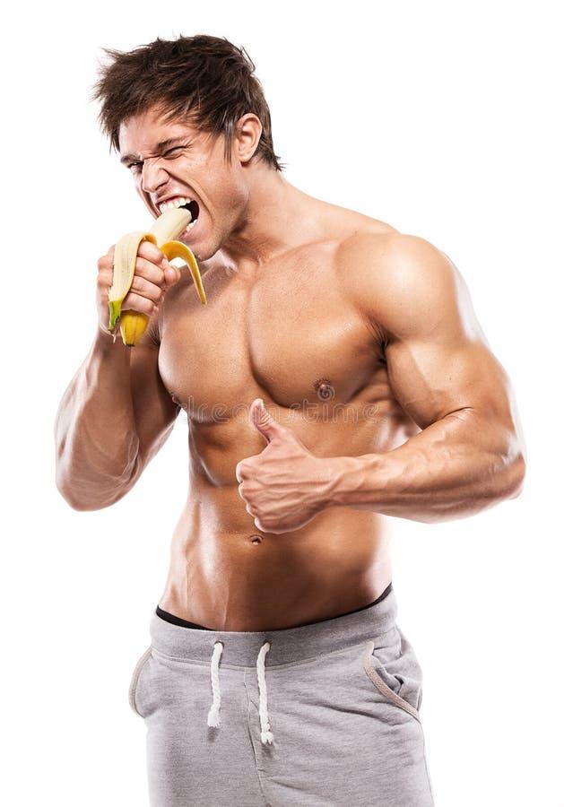 Homme sportif fort montrant le corps musculaire et mangeant une banane photographie stock libre de droits