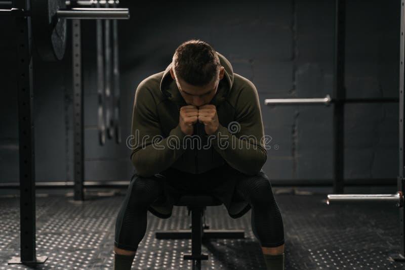 Homme sportif fort s'asseyant sur la panne de douleur de banc de gymnase pour surmonter image stock