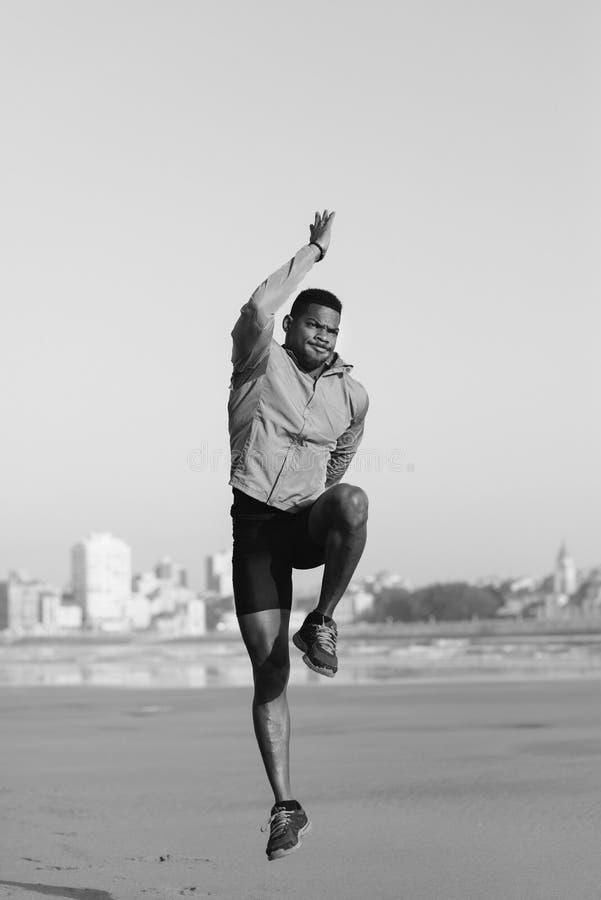 Homme sportif sautant pour réchauffer avant le fonctionnement images libres de droits