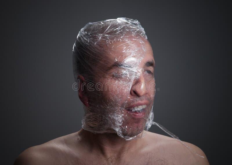 Homme suffoquant avec du plastique autour de sa tête images stock