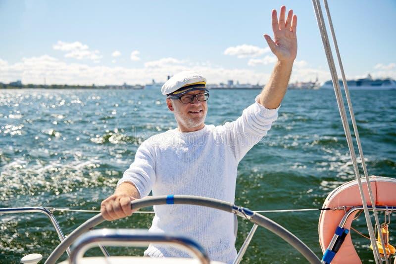 Homme supérieur à la barre sur la navigation de bateau ou de yacht en mer image stock