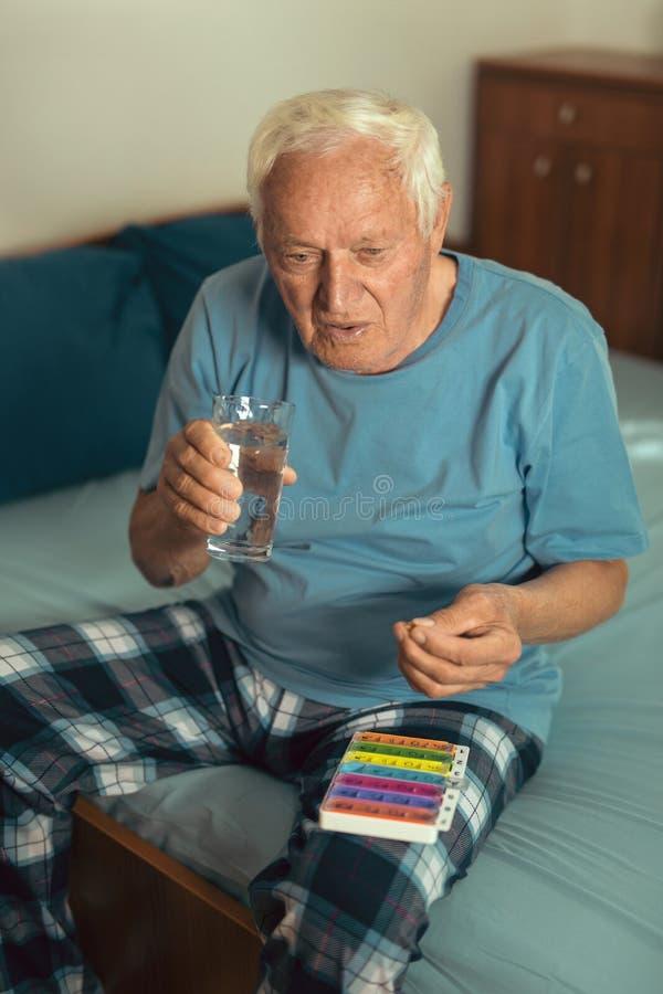 Homme supérieur à la maison prenant le médicament photo stock