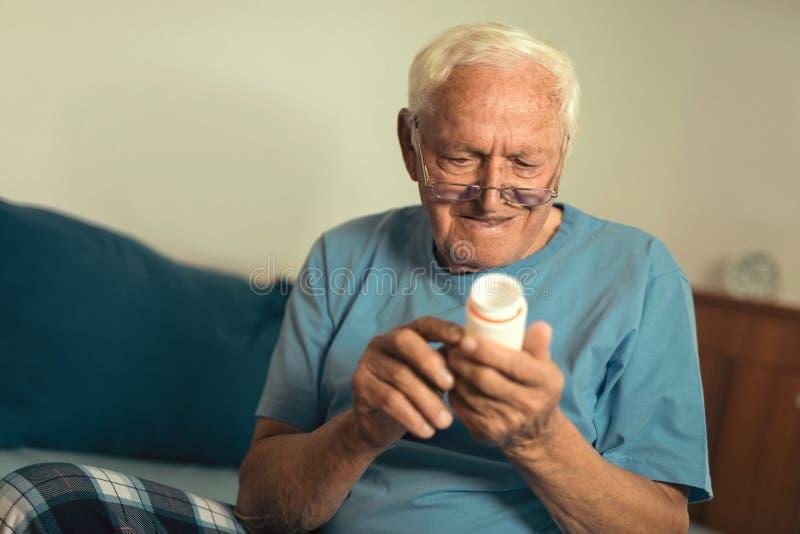 Homme supérieur à la maison prenant le médicament photos libres de droits