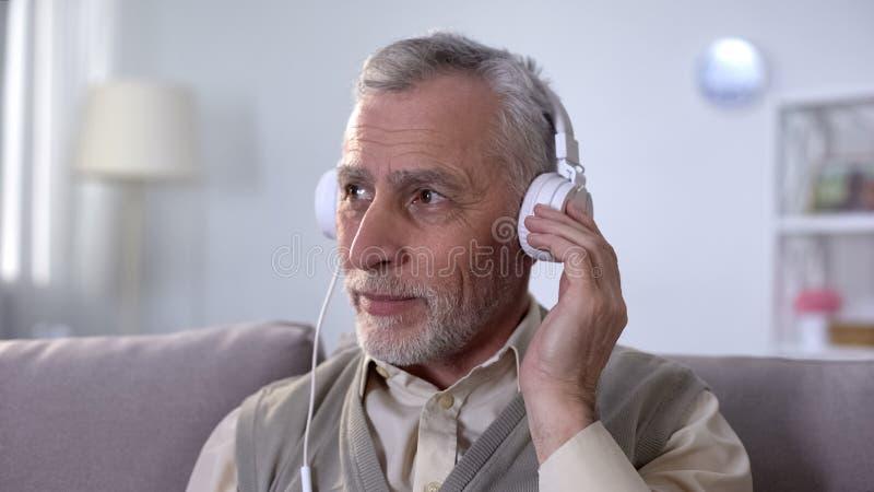 Homme supérieur écoutant la musique dans des écouteurs, temps libre avec plaisir, passe-temps photos stock