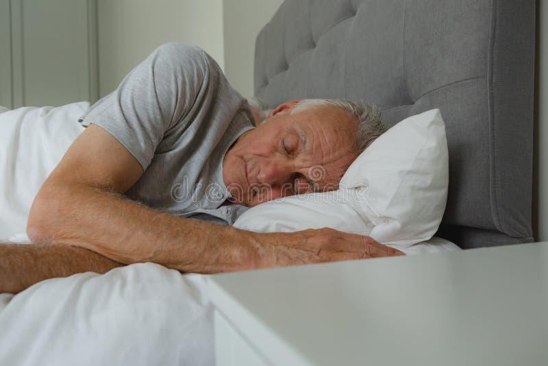 Homme supérieur actif dormant dans le lit dans la chambre à coucher photos stock