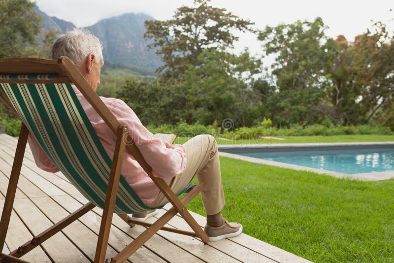 Homme supérieur actif lisant un livre tout en détendant sur le canapé du soleil dans l'arrière-cour photo libre de droits