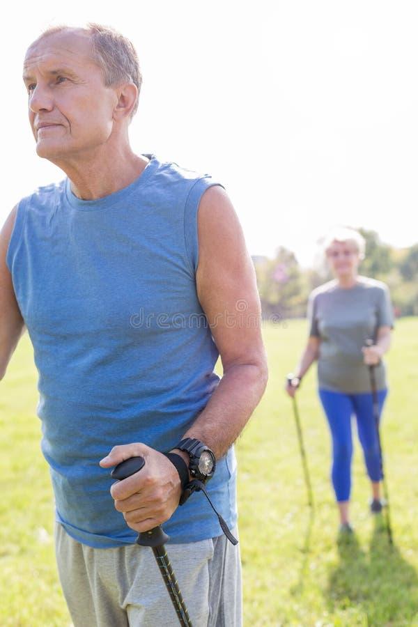 Homme supérieur actif marchant avec la femme en parc images stock
