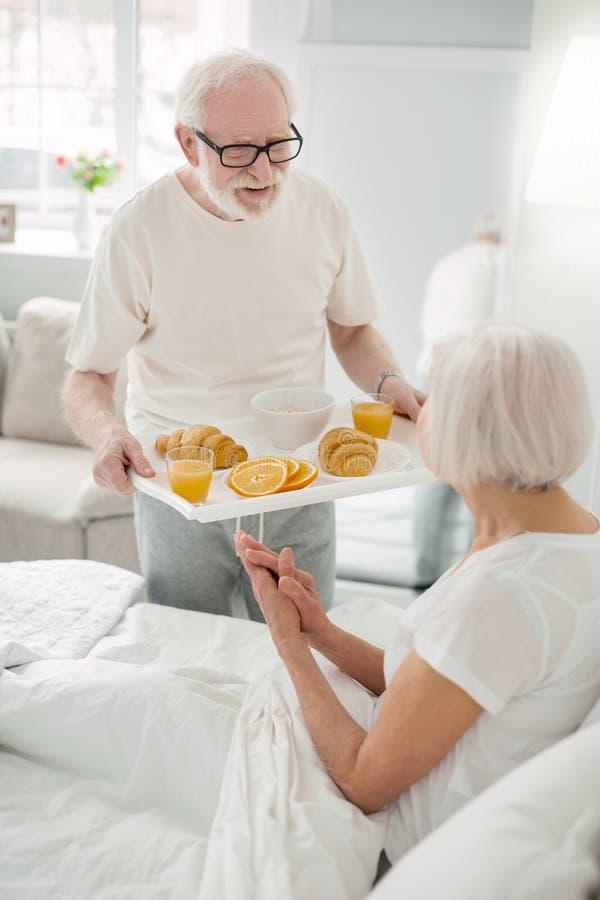 Homme supérieur agréable tenant un plateau avec la nourriture images stock
