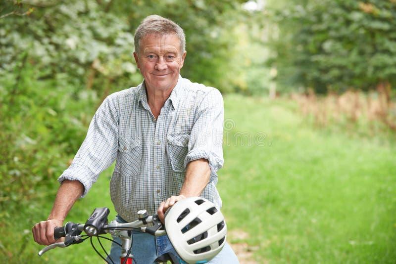 Homme supérieur appréciant le tour de cycle dans la campagne image stock