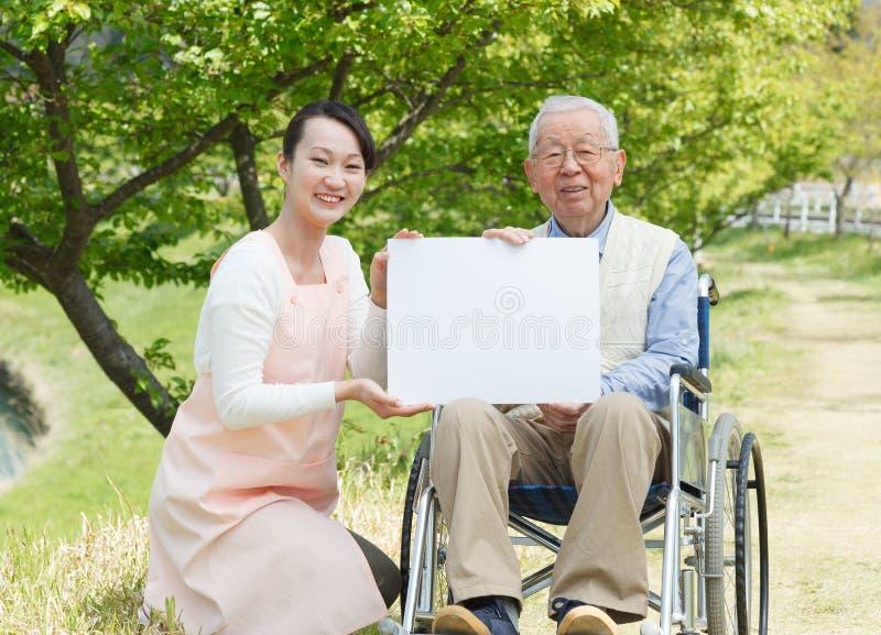 Homme supérieur asiatique s'asseyant sur un fauteuil roulant avec le travailleur social et le conseil blanc photographie stock libre de droits
