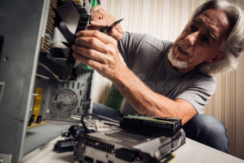 Homme supérieur assemblant un ordinateur de bureau images libres de droits