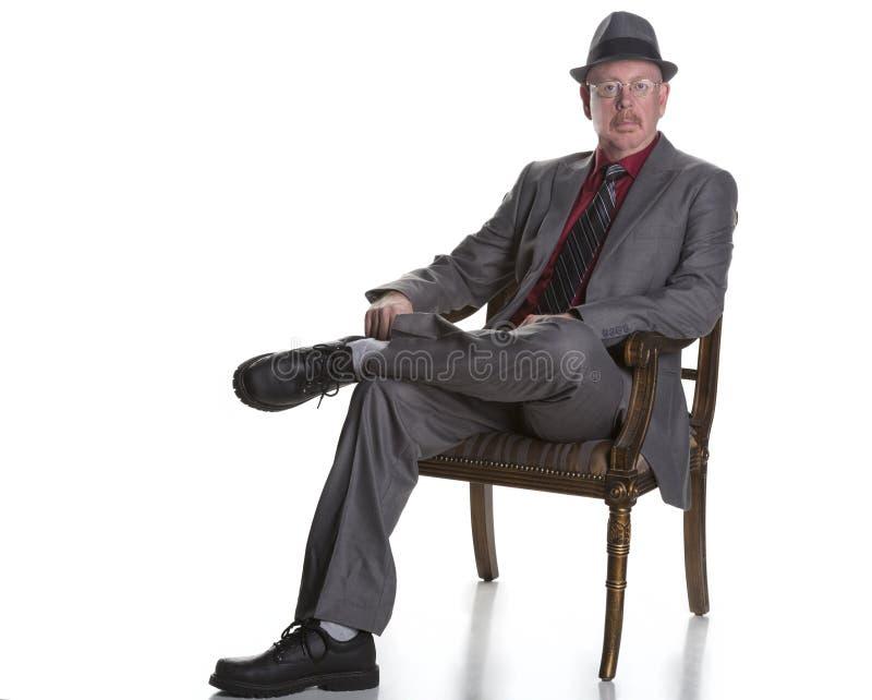 Homme supérieur assis d'isolement sur le blanc photos stock