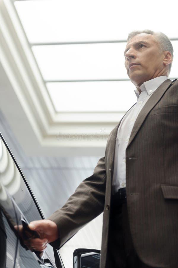 Homme supérieur au concessionnaire automobile. Homme d'affaires supérieur sûr o images libres de droits