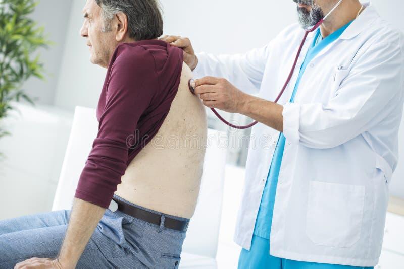 Homme supérieur au cours d'examen médical photographie stock libre de droits