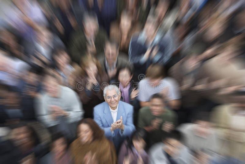 Homme supérieur avec des applaudissements de foule photo stock