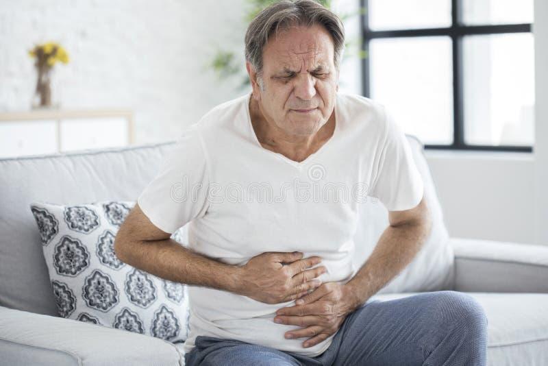 Homme supérieur avec douleur abdominale photos stock