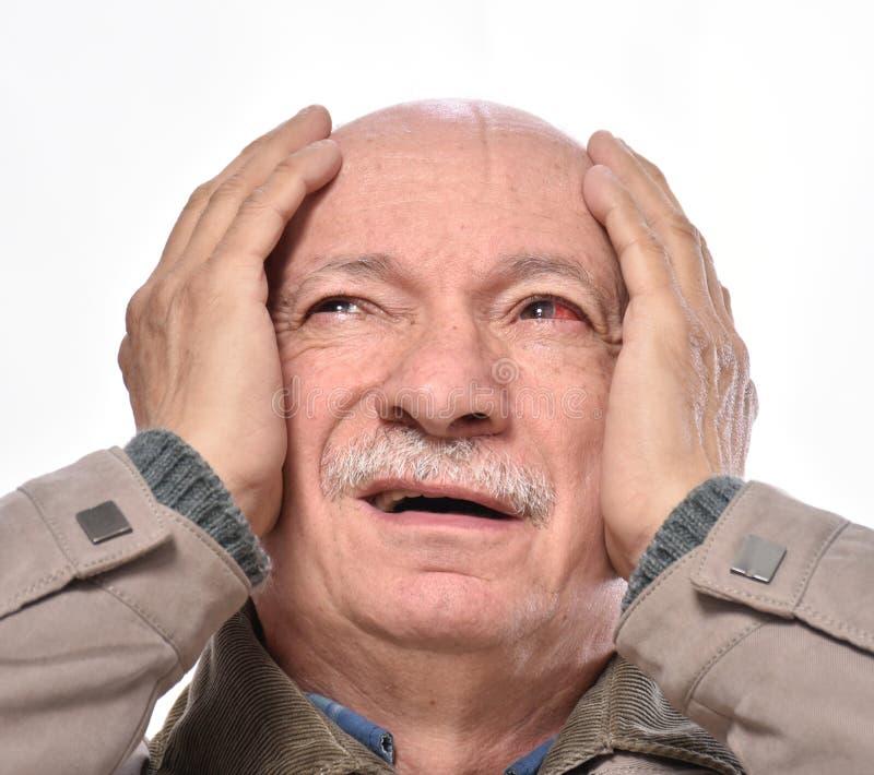 Homme supérieur avec l'oeil injecté de sang rouge irrité souffrant de la douleur photographie stock