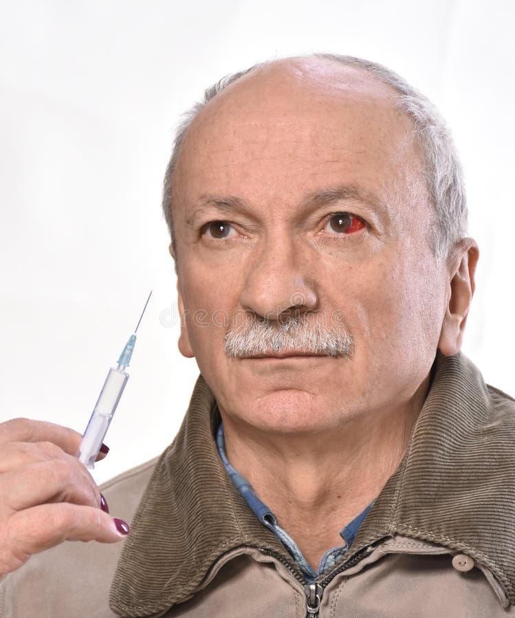 Homme supérieur avec la seringue rouge irritée de participation d'oeil injecté de sang photos libres de droits