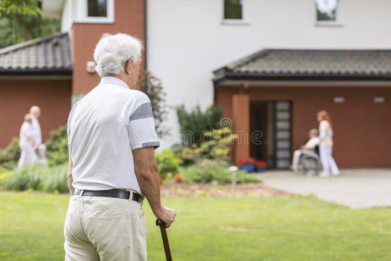 Homme supérieur avec le bâton de marche pendant le séjour dans une maison de soins Bl images stock